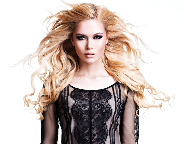 長い白い巻き毛と暗いアイメイクの若い美しい女性の肖像画。白い壁にポーズをとるファッションモデル