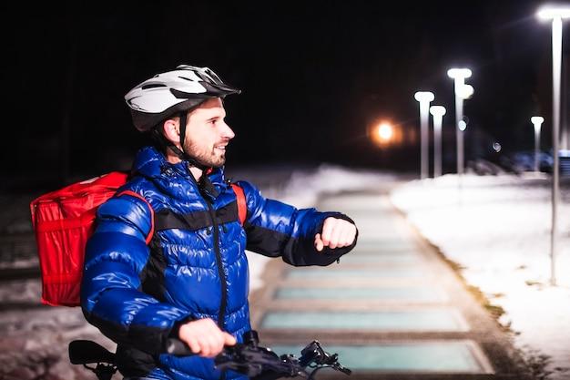 自転車を持った若い宅配便の肖像画は、ホログラフィックマップで未来的な画面に触れています。夕方に顧客の住所マップを表示します。デジタルマップ、ホログラム、未来、宅配。