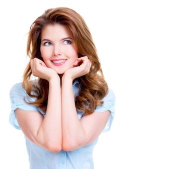 Портрет молодой счастливой вдумчивой женщины смотрит вверх - изолированный на белой предпосылке.