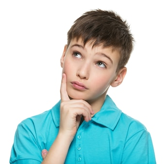 Портрет молодого улыбающегося думающего мальчика-подростка смотрит вверх в повседневной одежде - изолированном на белом.