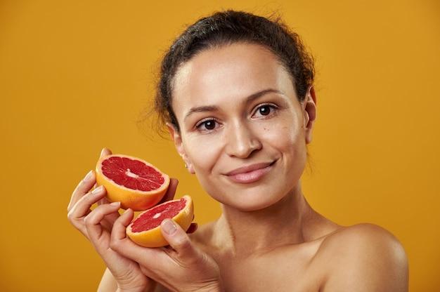 Портрет молодой женщины афроамериканца на желтом фоне с грейпфрутом
