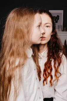 白いシャツを着た姉と妹の肖像画。