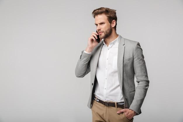 Портрет думающего красавца в куртке, говорящего по мобильному телефону, изолированного над белой стеной