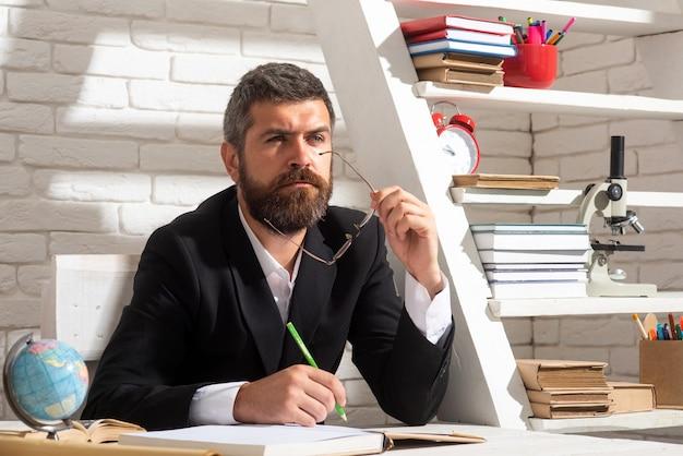 학교 교실에서 생각하는 남성 교사의 초상화. 학교 교실에서 책에 텍스트를 작성하는 책상에 앉아 교사.