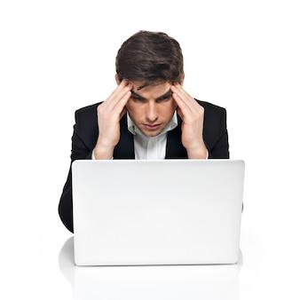 Портрет мышления офисного работника с ноутбуком, имеющим стресс, сидя на столе, изолированном на белом.