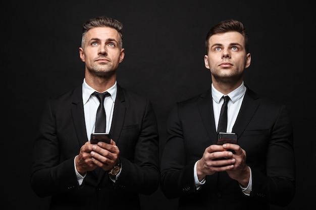 Портрет думающих двух бизнесменов, одетых в строгий костюм, смотрящих вверх и держащих мобильные телефоны, изолированные на черной стене Premium Фотографии