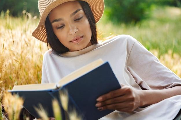 Портрет думающей женщины с пирсингом в губе и соломенной шляпе, читающей книгу, лежа на траве в зеленом парке