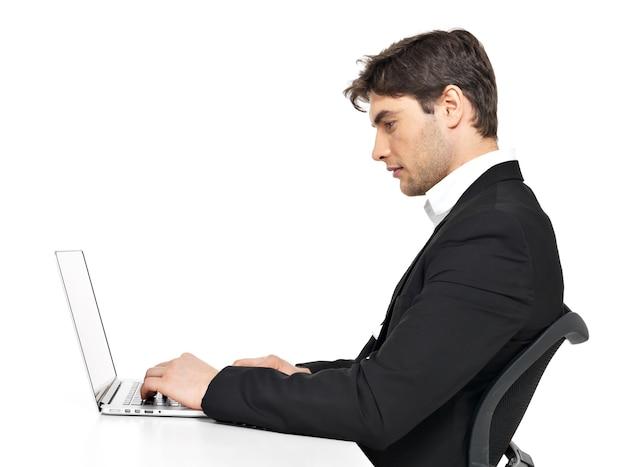白で隔離のテーブルに座っているラップトップを持つ若いサラリーマンを考える肖像画。
