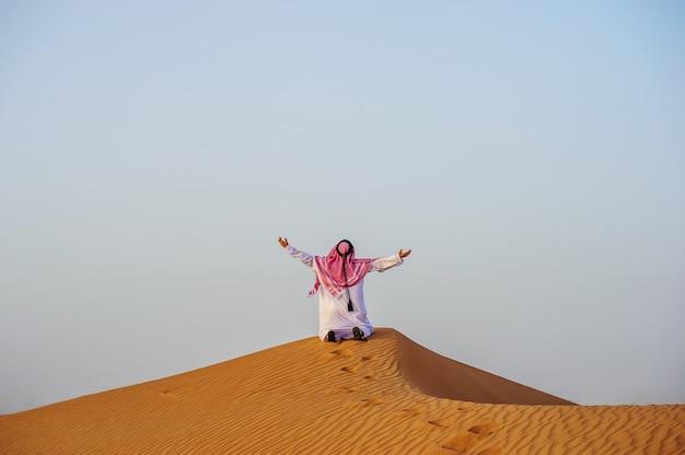 노란 사막 한가운데 목 마른 아랍 남자의 초상화.
