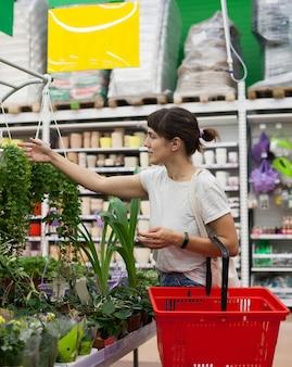 鉢植えの屋内花を持つ部門の近くのスーパーマーケットで30歳の女性の肖像画