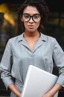 手にラップトップを手に、夢のように立っている眼鏡の思慮深いアフリカ系アメリカ人の女の子の肖像画