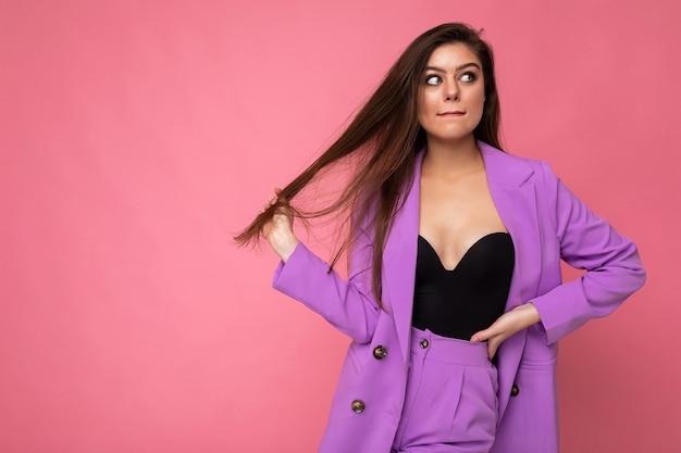 Портрет вдумчивой красивой модной брюнетки в повседневной модной фиолетовой куртке