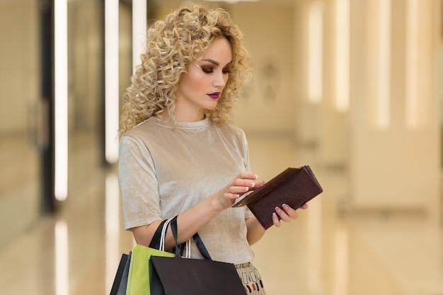 Портрет вдумчивого красивого человека, держащего открытый бумажник с задумчивым выражением лица в торговом центре с магазинами на фоне. молодая женщина с бумажными пакетами решает расходы во время покупок