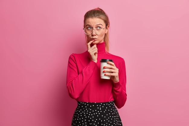 上に集中している思慮深い美しい10代のヨーロッパの女の子の肖像画は使い捨てのコーヒーを保持