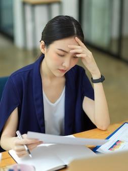 Портрет вдумчивых деловых женщин, работающих на своем столе в офисе и усталых от напряженной работы