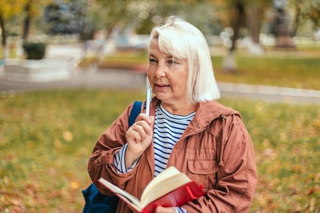 Портрет вдумчивой сконцентрированной занятой пожилой женщины с блокнотом и ручкой в руках, планирующей экспертизу, анализирующей прогулки в осеннем парке.