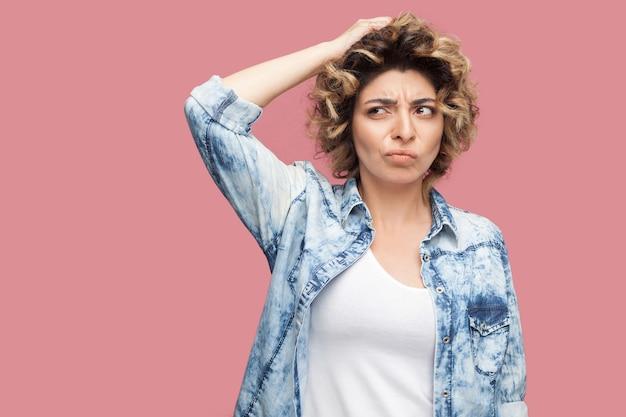 Портрет задумчивой запутанной молодой женщины с вьющейся прической в повседневной синей рубашке стоит, почесывая голову и думая, что делать. крытая студия выстрел, изолированные на розовом фоне.