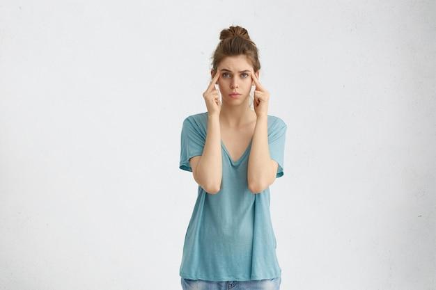 思いやりを集めようとする思慮深い女性の肖像画。寺院に指を置き、分離された青い暖かい目で直接見ています。人、ライフスタイルのコンセプト