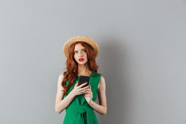 麦わら帽子と灰色の壁に分離されたスマートフォンを手に脇を見て緑のドレスを着ている思いやりのある生姜女性の肖像画