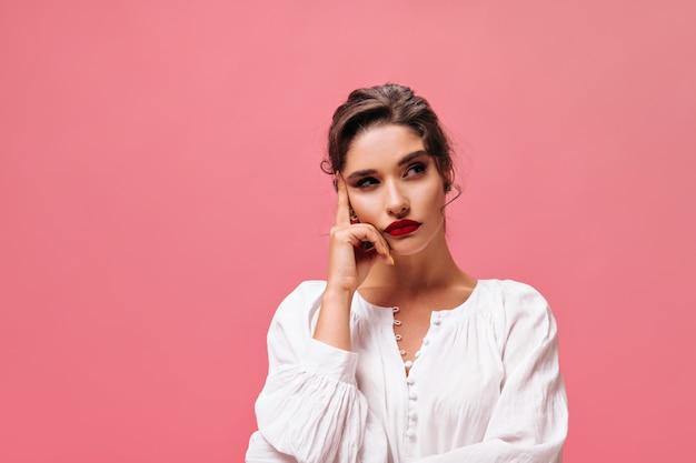 ピンクの背景に赤い唇を持つ思いやりのある女の子の肖像画。カメラでポーズをとる白いスタイリッシュなブラウスの真面目な若い女性。