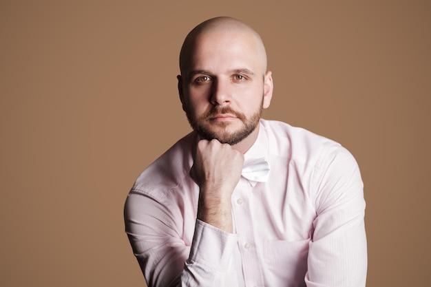 Портрет вдумчивого красивого бородатого лысого мужчины в светло-розовой рубашке и белом луке, сидящего на стуле и смотрящего в камеру с серьезным думающим лицом. крытая студия выстрел, изолированные на коричневом фоне.