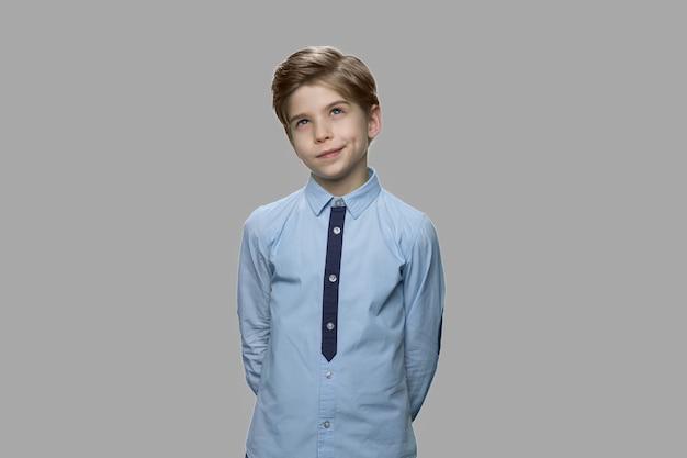 Портрет заботливого маленького мальчика. десятилетний мальчик мечтает на сером фоне.