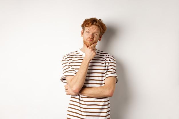 考え、左上隅を見て、選択をし、白い壁の上に立っている赤い髪の思いやりのある男の肖像画