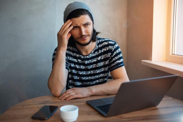 窓の近くのラップトップの家で働く思いやりのある男の肖像画。木製のテーブルの上のスマートフォンとコーヒーカップ。
