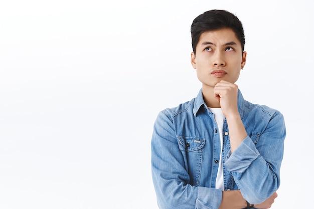 思慮深い賢いアジア人男性の肖像画、困惑した男子生徒の解決、複雑なまたは熟考、作り上げられたアイデアを試している間あごに触れる、白い壁の上で空想