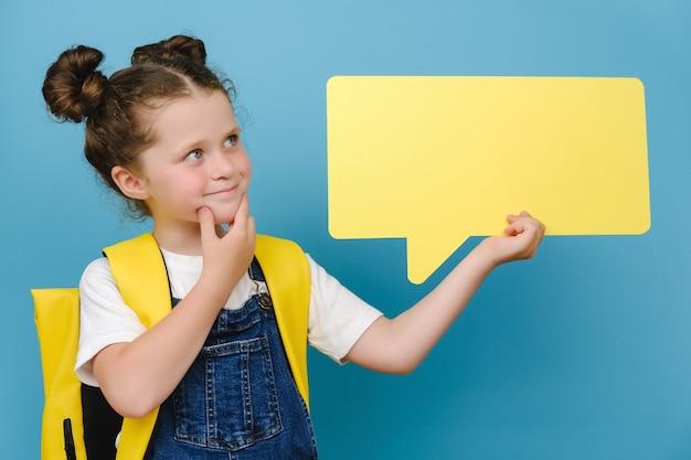 머리 위에 노란색 빈 말풍선을 들고 있는 사려깊은 미소 짓는 백인 여학생의 초상화, 배낭을 메고 광고를 위한 복사 공간이 있는 파란색 스튜디오 배경 위에 고립된 포즈