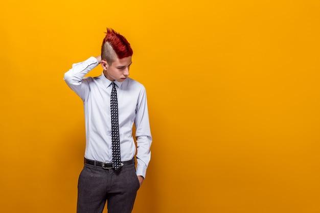Портрет вдумчивого мальчика-подростка смотрит вниз и позирует в помещении.
