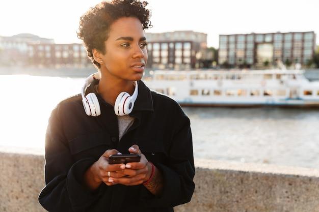 川沿いを歩きながらスマートフォンを持って巻き毛のアフロ髪型の思いやりのある女性の肖像画