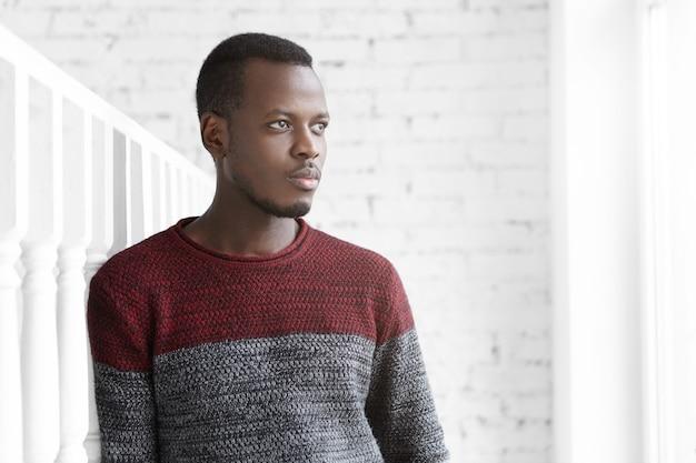 白い部屋に何気なく立っている服を着た思慮深い若いアフリカ系アメリカ人エンジニアの肖像画