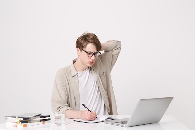 Портрет вдумчивого молодого человека-студента в бежевой рубашке и очках выглядит сосредоточенным и учится за столом, используя портативный компьютер и ноутбуки, изолированные на белой стене