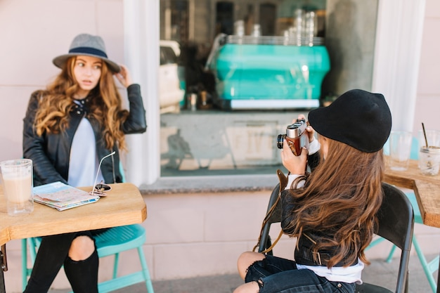 彼女の娘が彼女の写真を撮っている間コーヒーを飲みながらテーブルに座っているフェルト帽子で思いやりのある若い女性の肖像画。