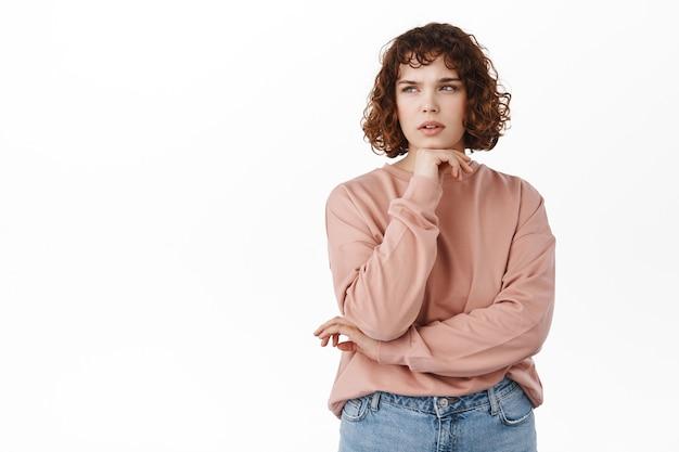 Портрет мыслящей кудрявой девушки, студентки, делающей предположение, серьезной и думающей, смотрящей в верхний левый угол, сосредоточенной, обдумывающей решение, стоящей на белом