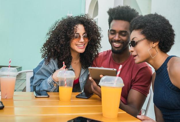 一緒に楽しんで、カフェテリアで屋外でデジタルタブレットを使用している3人のアフロの友人の肖像画。技術コンセプト。