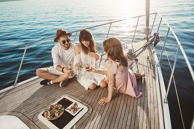 요트의 보드에 앉아 샴페인을 마시고 유쾌하게 얘기하면서 저녁을 즐기는 세 매력적인 유럽 사람들의 초상화. 친구들은 일 년 내내 열심히 일하면서 마침내 태양과 바다를 즐기 었습니다