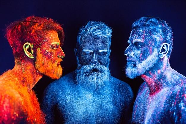 Портрет трех бородатых мужчин, окрашенных в флуоресцентные порошки.