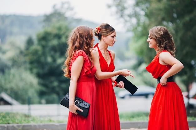 赤いドレスの3つの美しい花嫁介添人の肖像画