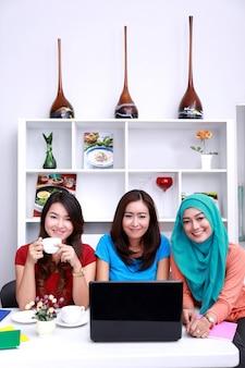 Портрет трех красивых студентов колледжа, улыбающихся и обучающихся вместе в гостиной