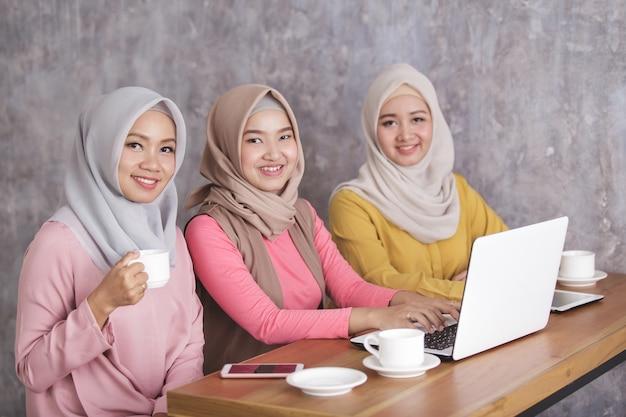 コーヒーショップで一緒に彼らのラップトップに取り組んでいる3人の美しいイスラム教徒の女性の肖像画