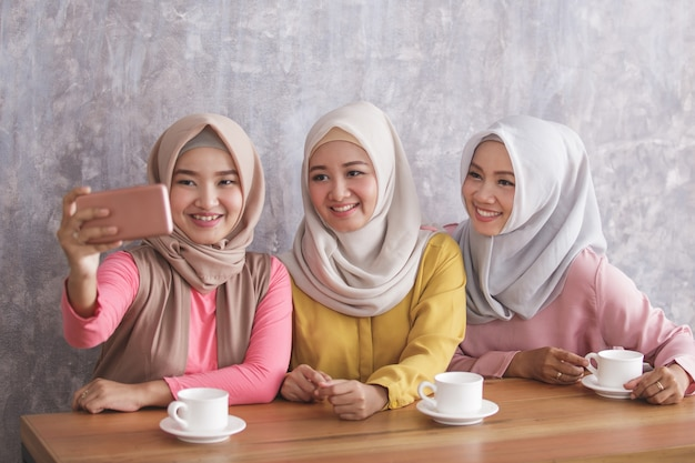 カフェで一緒に自分撮りをしている3人の美しい兄弟の肖像画