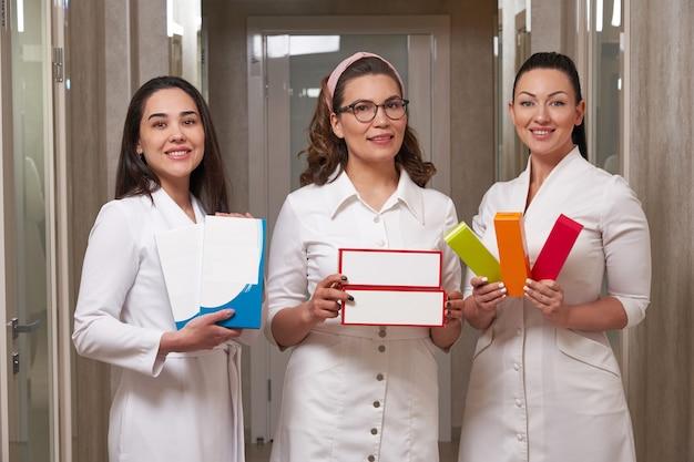 ボックスを保持している白いコートの美容師を身に着けている3人の美しい笑顔のブルネットの医師の肖像画