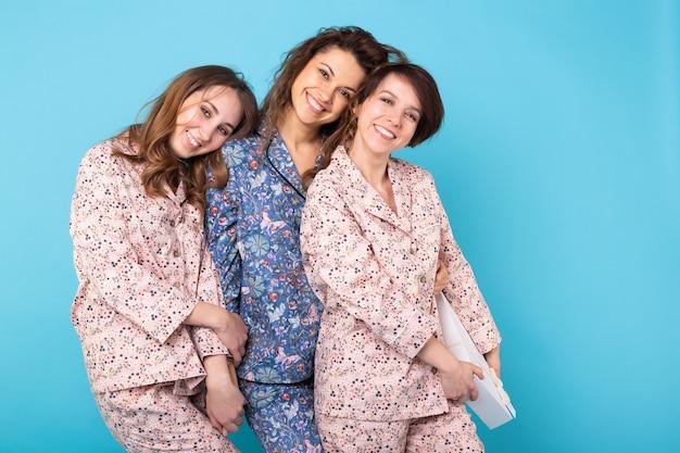 Портрет трех красивых молодых девушек в ярких пижамах, развлекающихся во время ночевки