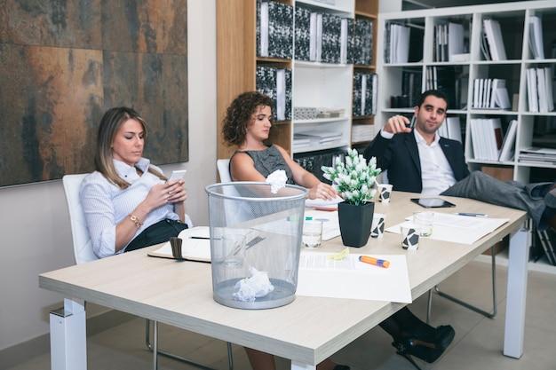 Портрет трех коллег скучно за столом в офисе, а бизнесмен бросает бумагу в корзину Premium Фотографии