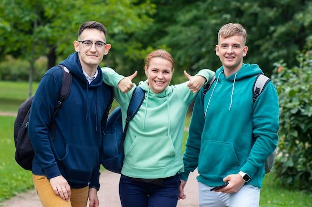 公園の屋外でバックパックを持っている3人の大学生の肖像画