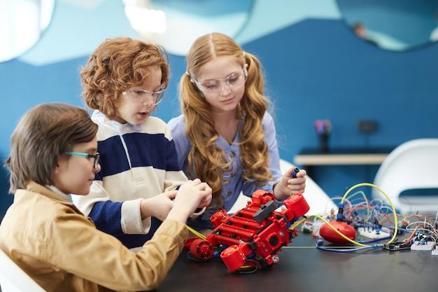 Портрет трех симпатичных детей, которые вместе строят робота, наслаждаясь уроками инженерии в школе развития