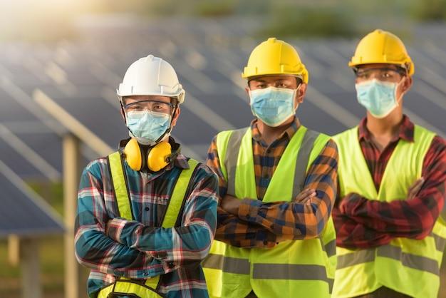タイのフェイスマスクを着用した建設現場での3人のエンジニアの肖像画