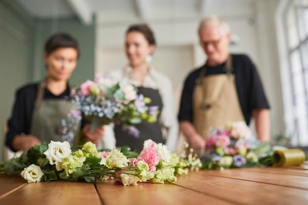 Портрет трех флористов, расставляющих цветочные композиции на деревянном столе в уютной мастерской, не ...